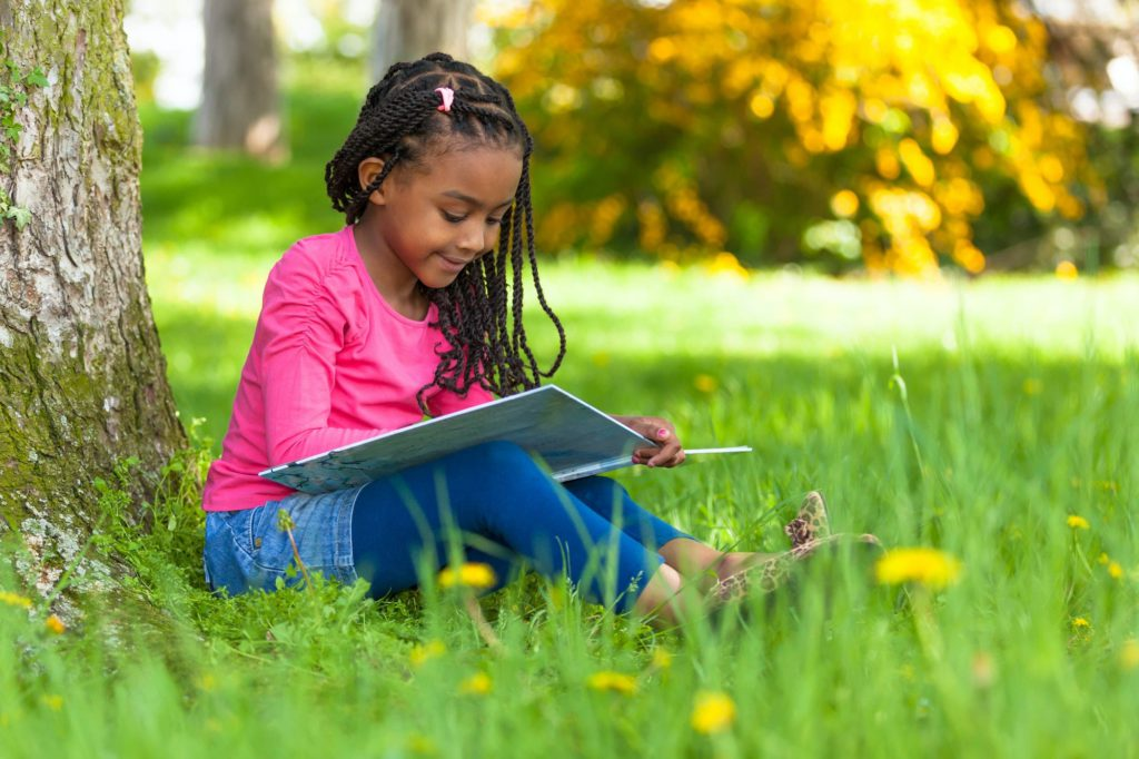Outdoor portrait of a cute young black little girl reading a boo